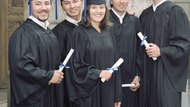Group of young graduates standing holding degrees