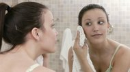 Woman drying face with towel in mirror