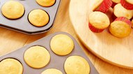 Fresh cupcakes in muffin tins and on lazy susan