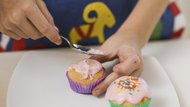 Girl spreading frosting on cupcakes
