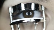 Close up of woman's eye and eyelash curler