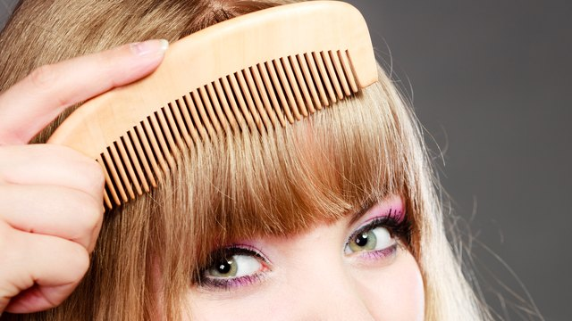 Closeup woman combing her bangs with comb