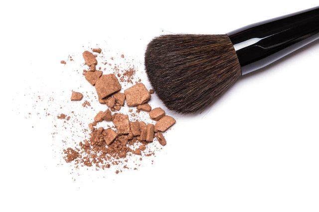 Bronzing powder with makeup brush on white background