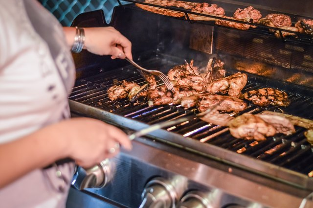 Grilling meat on gas barbecue close up
