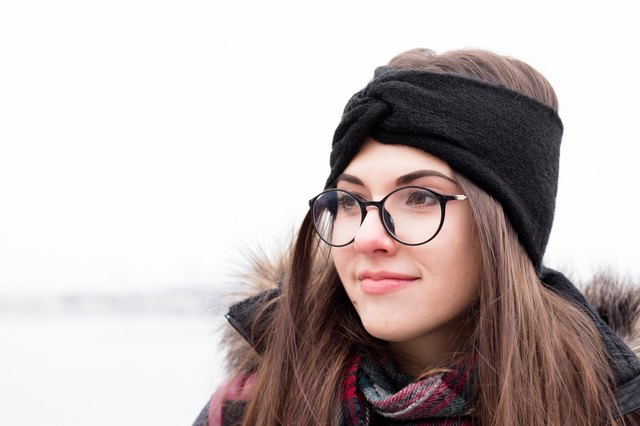 Girl in winter clothes, glasses and warm knitted headband. Portrait of beautiful young woman. Background of nature. Outdoor.