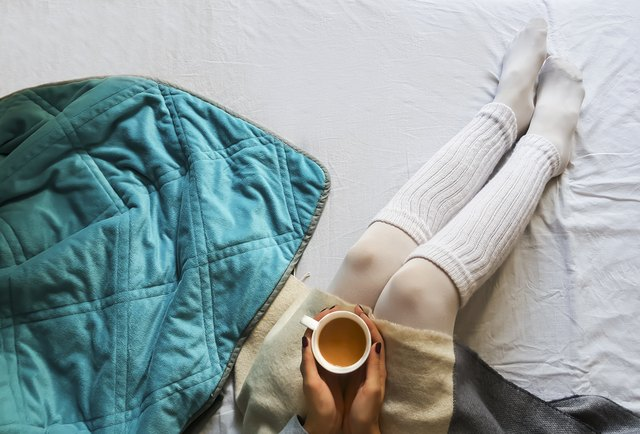 girl holding a cup of coffee in bed