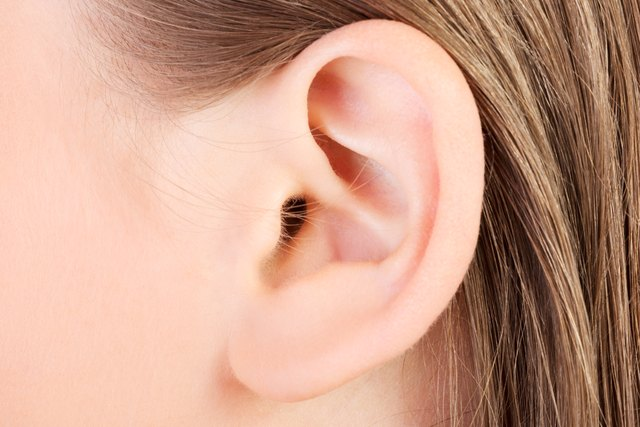 Close-up of an ear lobe of a person with blond hair