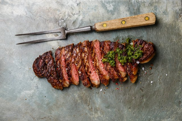 Sliced steak with chimichurri sauce and meat fork