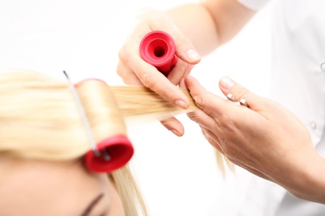 Hairdresser puts hot rollers in client's hair