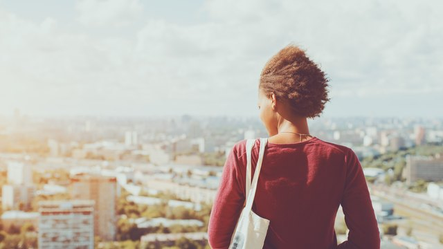 Rear view of curly black girl and cityscape