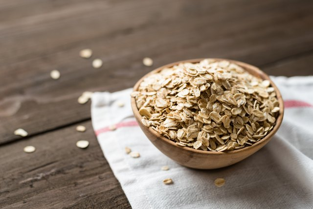 Oat flakes in old wooden bowl