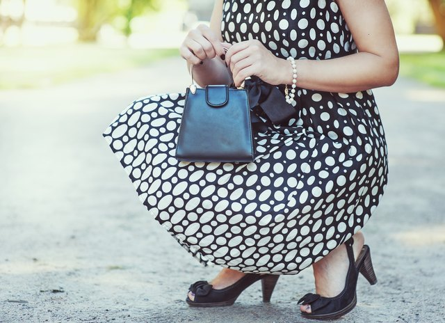 Fashionable woman with small bag in hands and dress sitting