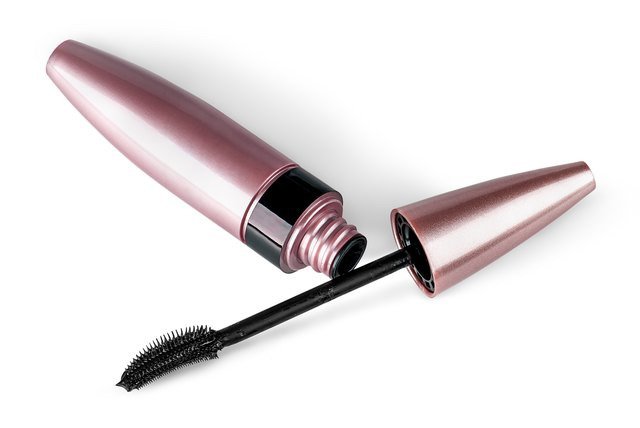 Mascara and brush lying beside