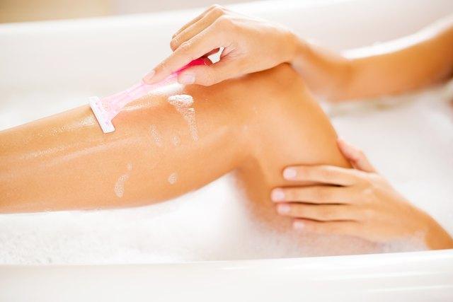 Woman shaving her legs in bath