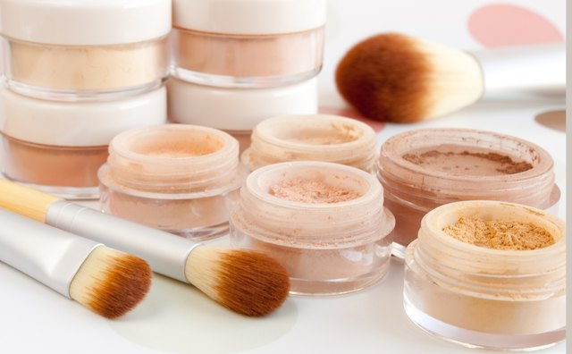 Pots of mineral make up with cosmetic brushes