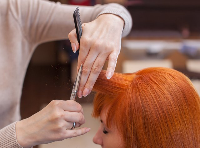 hairdresser cuts bangs for a female client