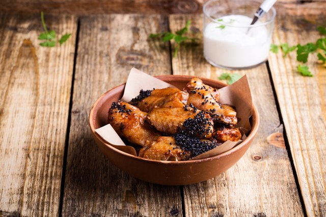 Glazed spicy chicken wings with sesame seeds with yoghurt dip