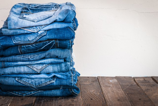 stack of various shades of blue jeans on old wood
