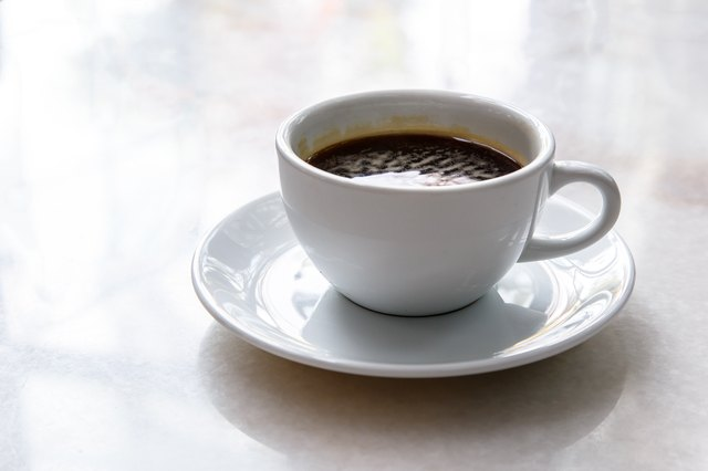 A cup of black coffee in a white cup on mable table