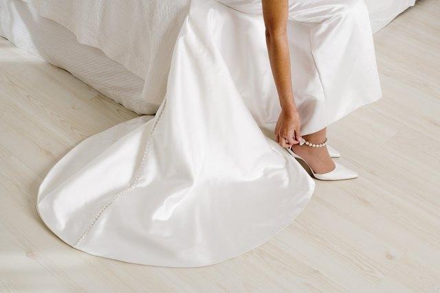 Bride adjusting strap of shoe