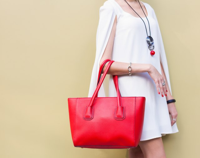 Fashionable big red handbag on the arm of the girl