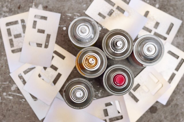six spray cans with stencil numbers