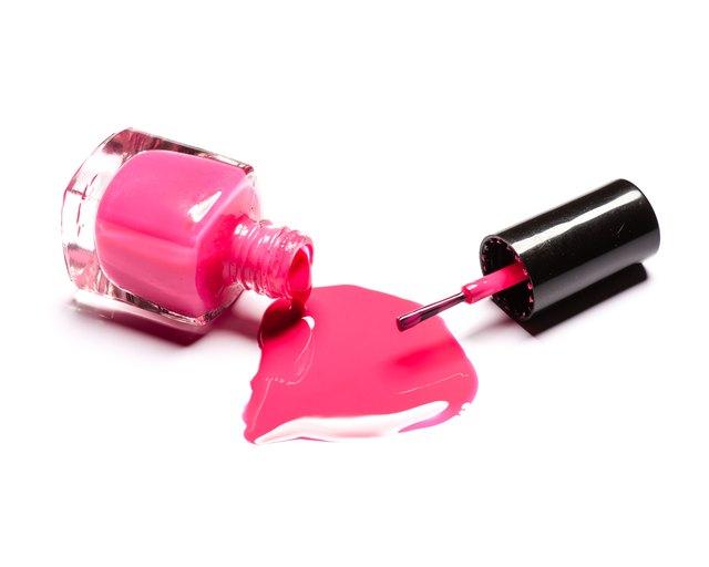 Pink nail polish and brush on white background