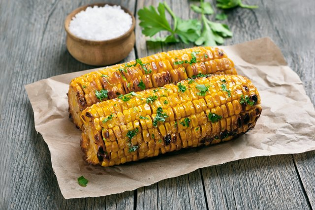 Grilled corn cobs on rustic table