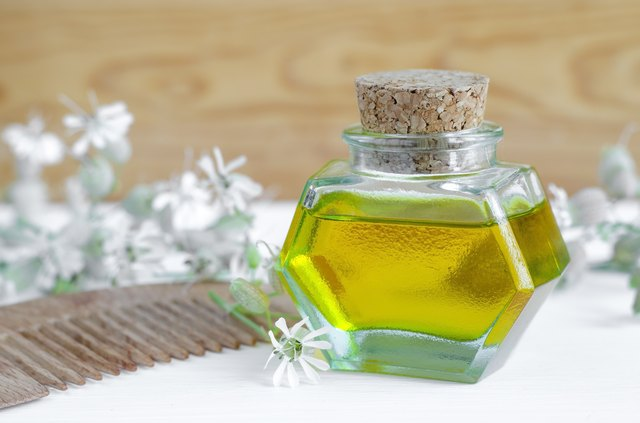 Bottle of cosmetic oil with flowers extract and hair comb