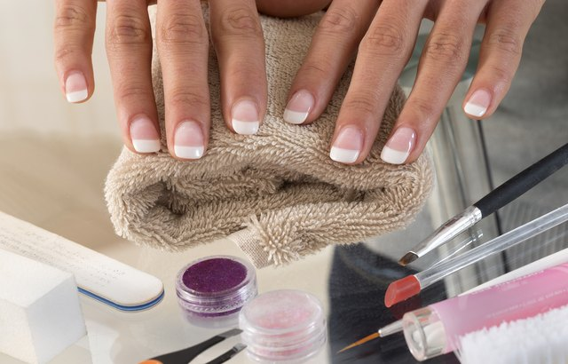 Hands of young woman with acrylic french manicure on the towel