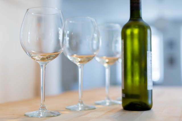 Three clear wine glasses and a bottle of chilled white wine on a wooden table