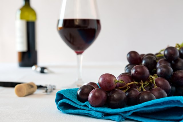 Closeup of red grapes and a glass of red wine
