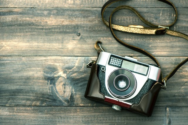 Vintage camera on wooden background. Retro style toned picture