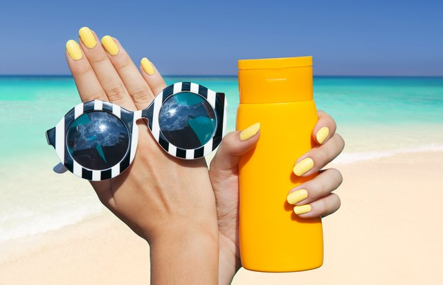 woman on the beach holding sunglasses and sunscreen lotion