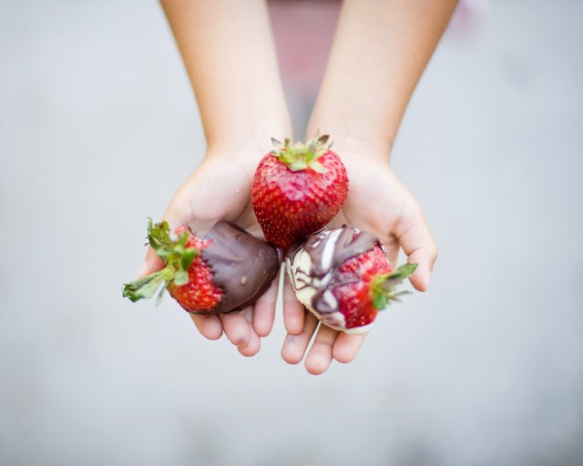 Chocolate dipped strawberries in hands
