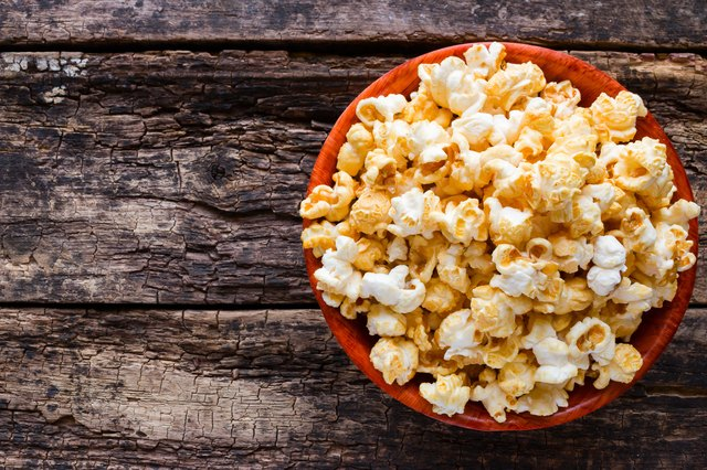 Popcorn in a bowl on a wooden background