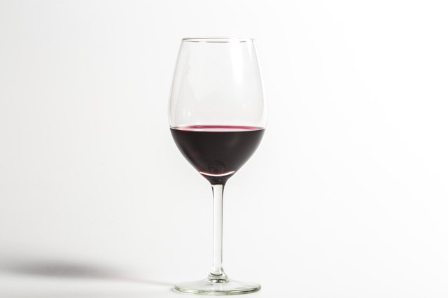 Red wine on a wineglass isolated on a white background