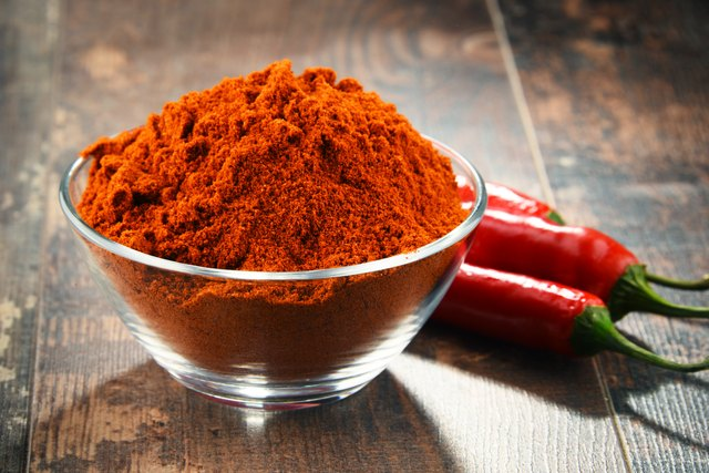 Bowl of cayenne pepper powder on wooden table