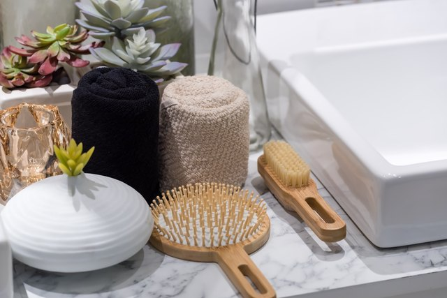 wood hair brush on a white marble bathroom counter