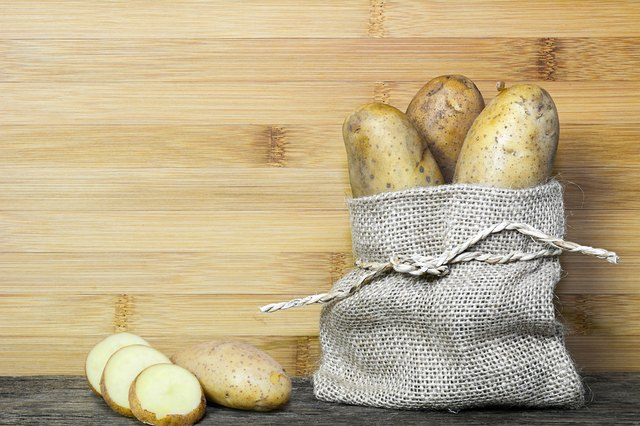 Raw potatoes in a bag and sliced on wooden