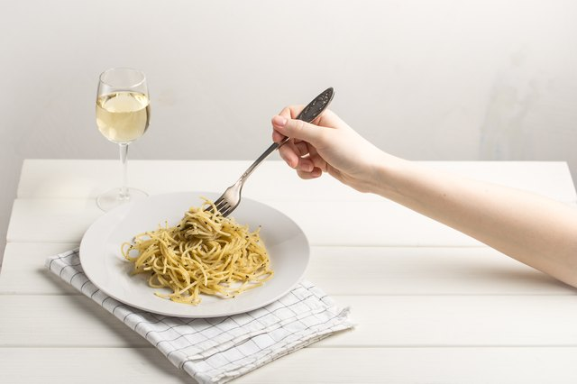 Hand holding fork with pasta and glass of white wine