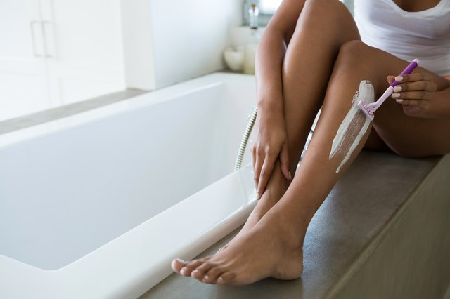 Low section of woman shaving leg in bathroom