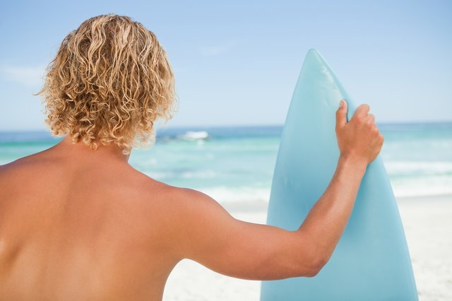 A young blonde man holding a perched surfboard