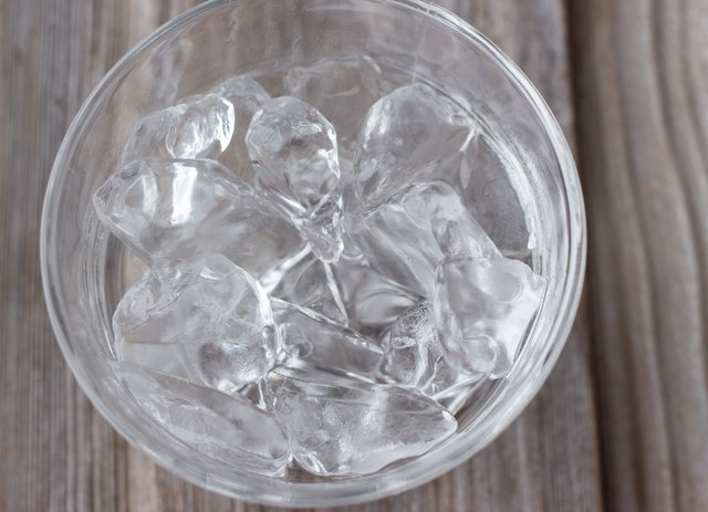 clear glass bowl with ice cubes on wood background