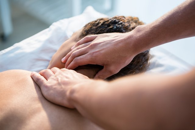 Chiropractor's hands working on a patient's neck