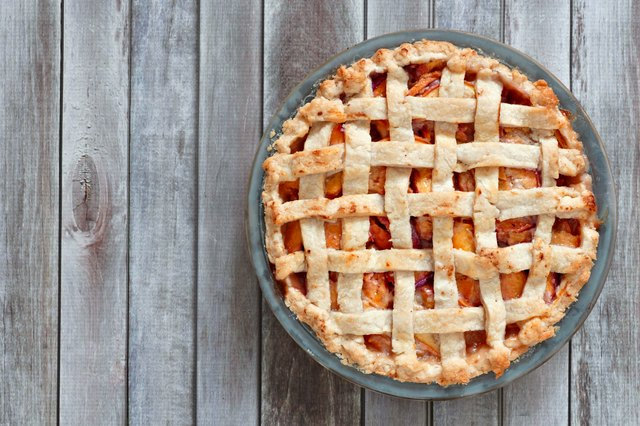 Rustic homemade peach pie, above view on wood