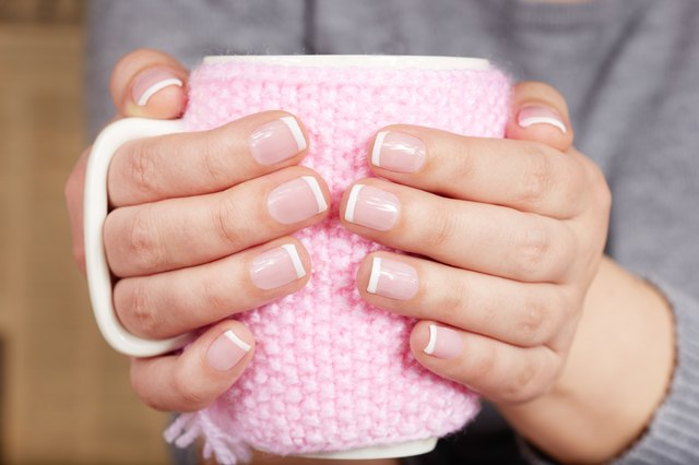 Hands with manicured nails holding a cup with knitted cover