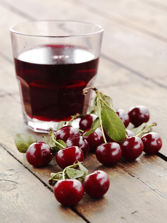 Cherries in original and liquid form set on a wooden table
