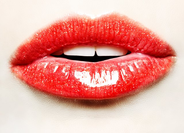 Beautiful female with red glittery lips close up
