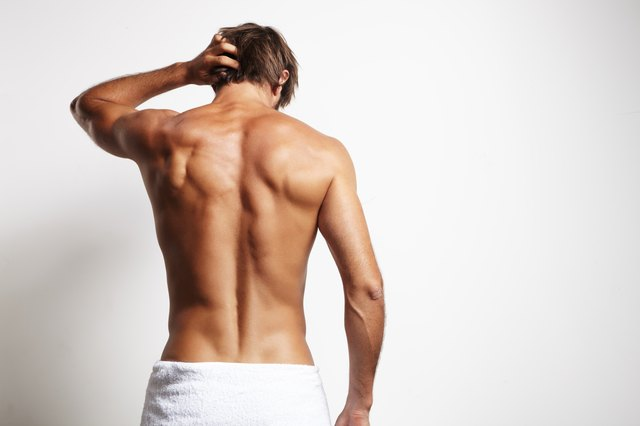 Muscular man from the back in white towel